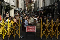 People react to being photographed as they sit outside on a street closed to traffic to try to reduce the spread of coronavirus so bars and restaurants can continue to stay open, in the Soho area of central London, Saturday, Sept. 19, 2020. (AP Photo/Matt Dunham)