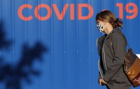 A woman wearing a face mask walks to get tested for COVID-19 at a sampling station in Prague, Czech Republic, on Sept. 18, 2020. (AP Photo/Petr David Josek)