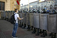 A young protester stands in front of police officers blocking the road against an opposition rally to protest the official presidential election results in Minsk, Belarus, on Sept. 20, 2020. (AP Photo/TUT.by)