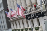 In this Jan. 3, 2020 file photo, the Wall St. street sign is framed by American flags flying outside the New York Stock Exchange in New York. (AP Photo/Mary Altaffer)