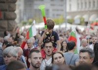 A father shouts slogans as he holds his son on his shoulders during a protest in front of the new National Assembly building, demanding government resignation in Sofia, Bulgaria, on Sept. 22, 2020. (AP Photo/Valentina Petrova)
