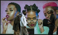 In this June 29, 2020, file photo, men in face masks walk past a hair product billboard on a street in Soweto, South Africa. (AP Photo/Themba Hadebe)