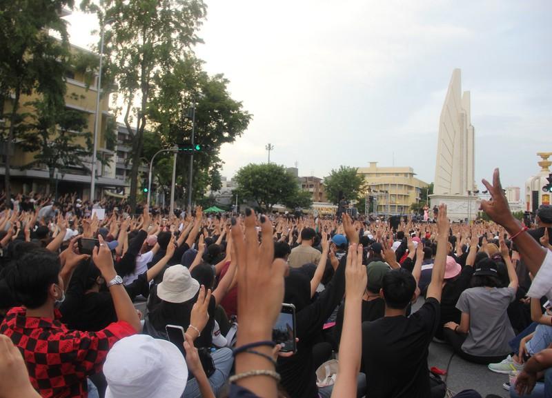 民主記念塔の前で行われた反政府集会の様子。参加者らは独裁への抵抗を意味する3本指のサインを掲げた=8月16日、バンコク