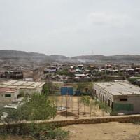煙が上るゴミ捨て場(奥)と住民がバラックで暮らすスラム(中央)、手前 の白い建物は子どもたちが通うアル・カイールアカデミー第2分校=2019年8月