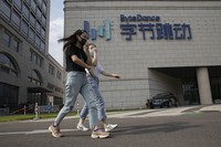 In this Aug. 7, 2020, file photo, women wearing masks to prevent the spread of the coronavirus chat as they pass by the headquarters of ByteDance, owners of TikTok, in Beijing, China. (AP Photo/Ng Han Guan, File)