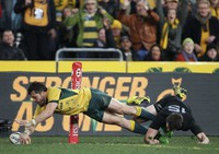 In this Aug. 8, 2015, file photo, Australia's Adam Ashley-Cooper, left, dives past New Zealand's Ben Smith to score a try during their Rugby Championship match in Sydney. (AP Photo/Rick Rycroft, File)