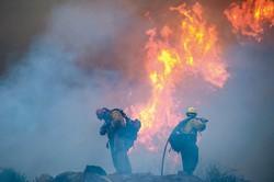 山火事で消化活動に当たる消防士 (Bloomberg)