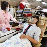 初めての献血をバスでする府立茨田高1年の上西りょうさん(16)。「ニュースで血液が足りないと知った。献血ができる16歳の誕生日を迎えたので、少しでも役に立ちたい思って来た。今後も続けて献血したい。若い世代に献血に協力しようと考える人が増えたらいい」と話す=大阪市鶴見区のライフ安田諸口店駐車場で2020年9月7日、北村隆夫撮影