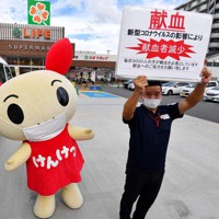 「地域のライフラインを支え、献血においても社会に貢献したい」と駐車場での献血バスの受け入れを始めたスーパーマーケット「ライフ安田諸口店」。検診車両の横で協力を呼びかける日本赤十字社のスタッフと献血推進キャラクター「けんけつちゃん」=大阪市鶴見区で2020年9月7日、北村隆夫撮影