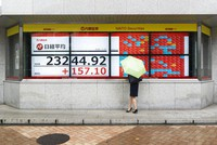 A woman looks at screens showing Japan's Nikkei 225 index at a securities firm in Tokyo on Sept. 25, 2020. (AP Photo/Hiro Komae)