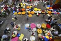 Flower vendors wait for buyers at a wholesale market in Bengaluru, India, on  Sept. 24, 2020. (AP Photo/Aijaz Rahi)