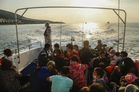 Migrants sit on a Turkish coast guard vessel after they were pulled off life rafts, during a rescue operation in the Aegean Sea, between Turkey and Greece, on Sept. 12, 2020. (AP Photo/Emrah Gurel)