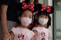 Young visitors wearing face masks look at the iconic cartoon characters Goofy and Pluto at the Hong Kong Disneyland, on Sept. 25, 2020. (AP Photo/Kin Cheung)