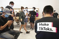 In this July 17, 2020, file photo, a visitor to an Apple store wears a t-shirt promoting Tik Tok in Beijing. (AP Photo/Ng Han Guan)