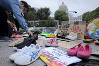 On Sept. 25, 2020, shoes and signs are seen lined up outside the National Diet Building in Tokyo as part of a