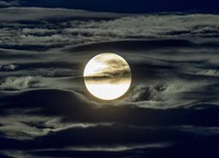 In this Sept. 2, 2020 file photo, the full moon shines surrounded by clouds in the outskirts of Frankfurt, Germany. (AP Photo/Michael Probst)