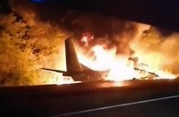 In this TV grab released by Ukraine's Emergency Situation Ministry, an AN-26 military plane bursts into flames after it crashed in the town of Chuguyiv close to Kharkiv, Ukraine, on Sept. 25, 2020. (Emergency Situation Ministry via AP)