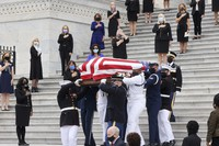 U.S. Congresswomen look on as the flag-draped casket of Justice Ruth Bader Ginsburg is carried out by a joint services military honor guard after lying in state at the U.S. Capitol on Sept. 25, 2020, in Washington. (Jonathan Ernst/Pool via AP)