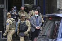 Hysni Gucati, the head of the War Veterans Organization of the Kosovo Liberation Army, is escorted by European Union security police officers from the offices of a war veterans association in Kosovo, in Pristina, on Sept. 25, 2020. (AP Photo/Visar Kryeziu)
