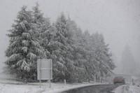 A car makes his way through heavy snow fall on motorway A 13 in Noesslach near Innsbruck, Austria, on Sept. 25, 2020. (AP Photo/Matthias Schrader)