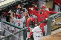 Cincinnati Reds' Mike Moustakas (9) is greeted in the dugout after his solo home run off Minnesota Twins pitcher Edwar Colina during the ninth inning of a baseball game on Sept. 25, 2020, in Minneapolis. (AP Photo/Jim Mone)