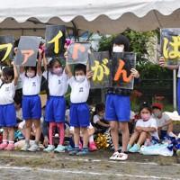 声援の代わりに「がんばれ」などと書かれた紙を掲げる児童たち=神奈川県相模原市の市立田名北小で2020年9月27日午前9時46分、滝川大貴撮影(画像の一部を加工しています)