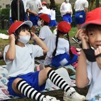 競技を終えて再びマスクを着ける児童たち。応援席では例年のように椅子を並べるのではなく、それぞれの児童が距離を保つために手持ちのレジャーシートを敷いていた=神奈川県相模原市の市立田名北小で2020年9月27日午前10時24分、滝川大貴撮影(画像の一部を加工しています)