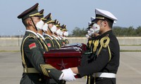 In this photo provided by the South Korea Defense Ministry, Chinese honor guard members, left, receive caskets containing the remains of Chinese soldiers from South Korean honor guards during the handing over ceremony at the Incheon International Airport in Incheon, South Korea, Sunday, Sept. 27, 2020. (South Korea Defense Ministry via AP)