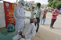 A health worker takes a nasal swab sample to test for COVID-19 test in Ahmedabad, India, Saturday, Sept. 26, 2020. (AP Photo/Ajit Solanki)