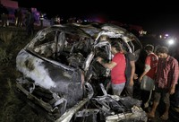 Rescue workers examine a burnt van at the accident site on a highway about 50 kilometers (31 miles) outside of Karachi, Pakistan, Saturday, Sept. 26, 2020. (AP Photo/Fareed Khan)