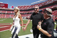 In this Sept. 16, 2018, file photo, Joe Montana and his wife, left, Jennifer walk onto the field at Levi's Stadium before an NFL football game between the San Francisco 49ers and the Detroit Lions in Santa Clara, Calif. (AP Photo/Tony Avelar)