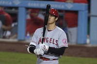 Los Angeles Angels designated hitter Shohei Ohtani looks at his bat before stepping up to the plate during the sixth inning of the team's baseball game against the Los Angeles Dodgers on Sept. 26, 2020, in Los Angeles. (AP Photo/Ashley Landis)