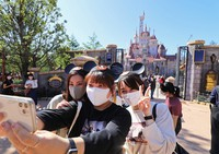 A visitor takes a selfie with her friends in front of the new attraction