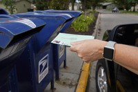 In this Aug. 18, 2020 photo, a person drops applications for mail-in-ballots into a mailbox in Omaha, Nebraska. (AP Photo/Nati Harnik)