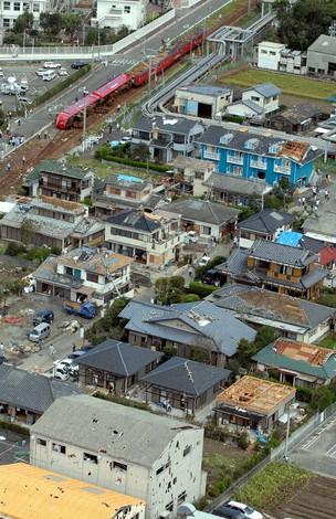 2006年9月の竜巻で被害を受けた宮崎県延岡市の住宅街。後方では特急「にちりん」の車両が脱線・横転している