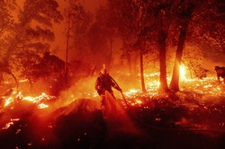 山火事の消火活動を行う消防士。専門家は、気候変動が米西部の山火事の規模や被害を拡大させていると指摘する=米カリフォルニア州で9月7日、AP