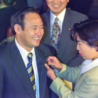 衆院選初当選後の1996年11月の特別国会召集日に初登院して職員に議員バッジをつけてもらう自民党の菅義偉氏=国会内で1996年11月7日撮影