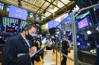 In this photo provided by the New York Stock Exchange traders gather at a post on the NYSE trading floor during the direct listing of Asana, on Sept. 30, 2020. (Courtney Crow/New York Stock Exchange via AP)