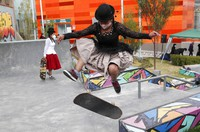 Aide Choque, wearing a mask amid the COVID-19 pandemic, is seen jumping with her skateboard during a youth talent show in La Paz, Bolivia, on Sept. 30, 2020.  (AP Photo/Juan Karita)