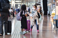 A child, center, is seen holding a toy airplane as their group heads for a flight in a domestic departures lobby in Tokyo's Haneda Airport on Oct. 3, 2020. (Mainichi/Daiki Takikawa)