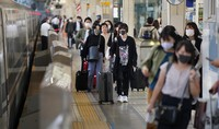 Travelers with their luggage are seen on a Tokaido Shinkansen bullet train platform at JR Tokyo Station during the first weekend that Go To Travel campaign subsidies were applied to the Japanese capital, on Oct. 3, 2020. (Mainichi/Tatsuro Tamaki)