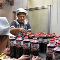 約3カ月ぶりの出荷に向けて看板商品の刺し身じょうゆ「老松」のボトルに手作業でラベルを貼る岩永醬油の従業員=熊本県芦北町で2020年9月26日、山崎あずさ撮影