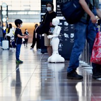 「Go Toトラベル」に東京が加わって初の週末。国内線出発ロビーで新型コロナウイルス感染拡大防止を呼びかける人型ロボット「Pepper」とジェスチャーする子ども=羽田空港で2020年10月3日、滝川大貴撮影