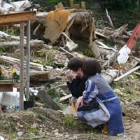 九州豪雨から3カ月。友人だった入江たえ子さんが犠牲となった土砂崩れ現場で目頭を押さえる女性たち。「いつも3人で一緒にいた。旅行したり、ご飯を食べたりして過ごした思い出が残る」と話した=熊本県芦北町で2020年10月4日、矢頭智剛撮影