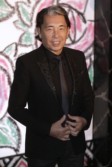 In this March 28, 2015 file photo, Japanese fashion designer Takada Kenzo poses for photographers as he arrives at the Rose Ball in Monaco. (AP Photo/Lionel Cironneau)