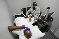 Larry Brown is tested by Dr. Jerry Smartt, on Aug. 17, 2020, in Carmel, Ind. (AP Photo/Darron Cummings)