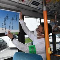 バスの車両内に防犯短歌のポスターを掲示する住之江署員=大阪市住之江区で、澤俊太郎撮影