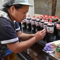 出荷に向けて看板商品の刺し身じょうゆ「老松」のボトルに手作業でラベルを貼る岩永醬油の従業員