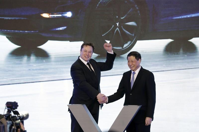 中国工場の開設で上海市長(右)と握手するテスラのイーロン・マスクCEO=2020年7月 Bloomberg