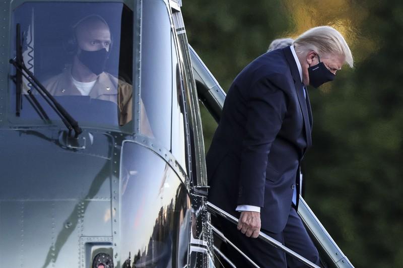 医療機関へ向かうため大統領専用ヘリ「マリーンワン」から降りるトランプ氏。その容体は日本にも大きく影響する(米メリーランド州で10月2日)(Bloomberg)